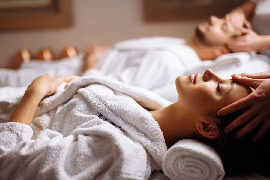 Young couple receiving head massage at beauty spa in New York NYC