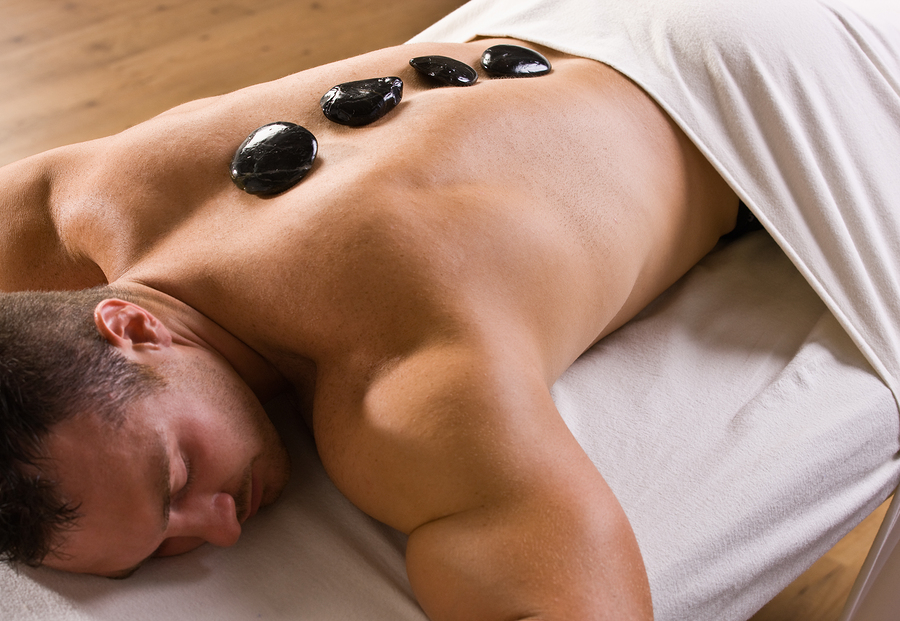 Man receiving hot stone therapy massage in New York NYC
