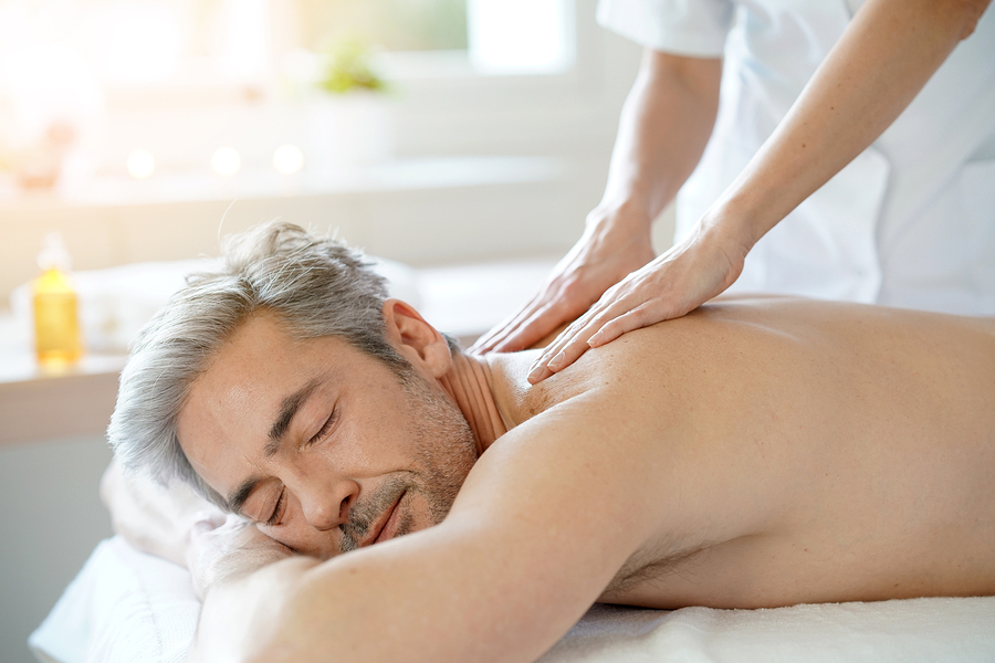 Man relaxing on massage table receiving massage Spa in New York City, NYC, Juvenex Spa