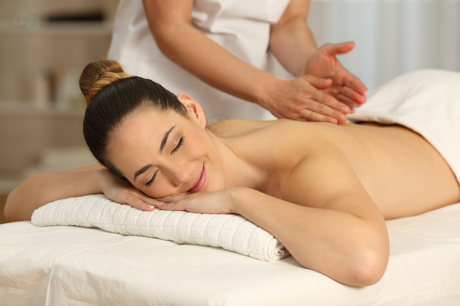 Happy woman relaxing receiving a massage in a spa salon in New York NYC