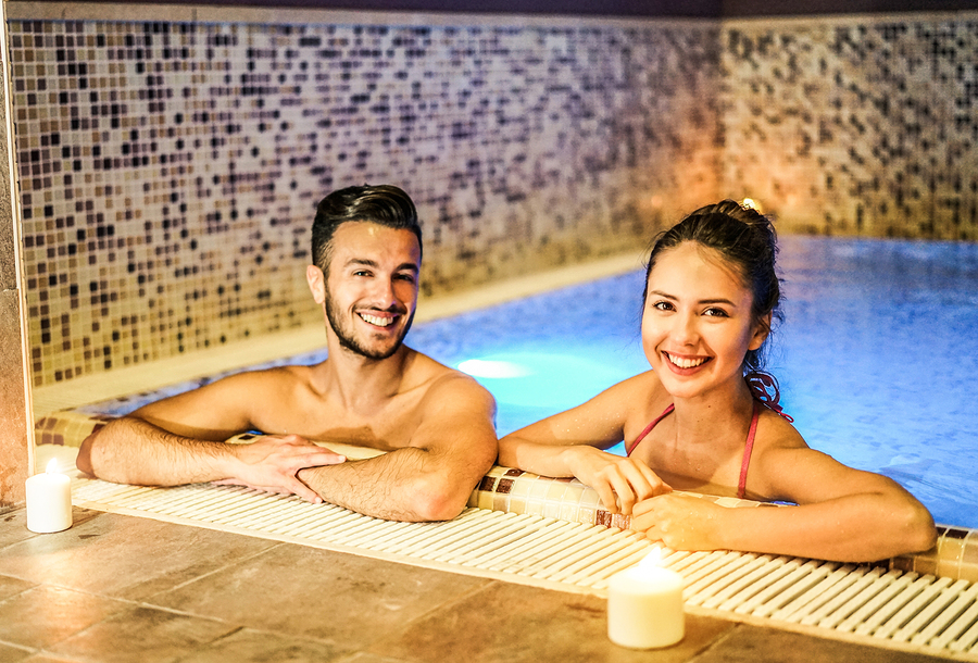 Young couple of lovers enjoying spa swimming pool - Romantic love story inside Spa massage in New York City