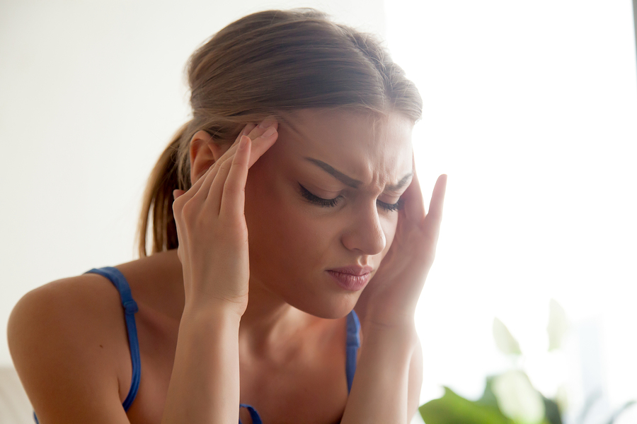 A young woman massaging temples with eyes closed, suffering from chronic migraine, stressed teenager experiencing sudden panic attack, feeling pain, head shot portrait, She might need have some full body massage in Juvenex Spa in New York, NYC