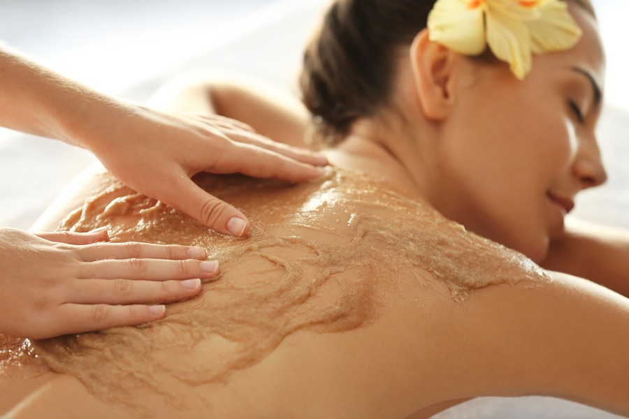 Young woman receiving scrub massage