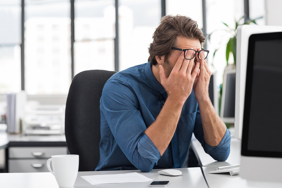 stressed businessman at desk in office.