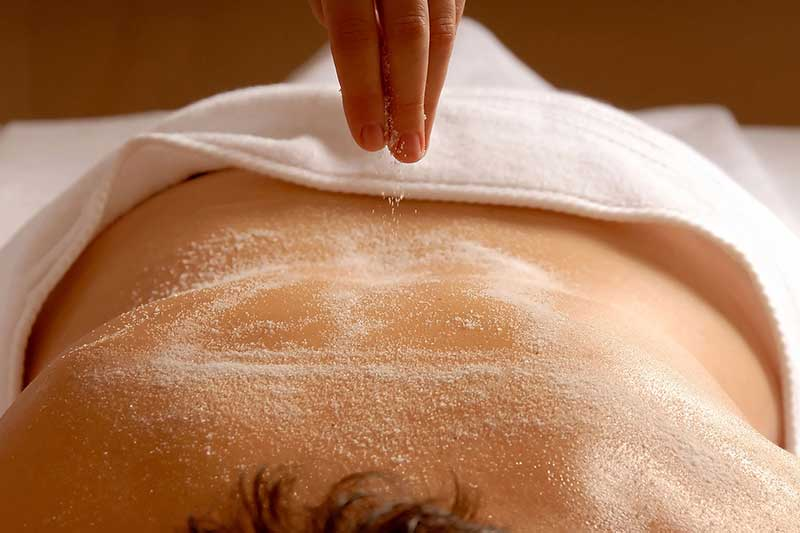 a person receiving a salt glow body scrub