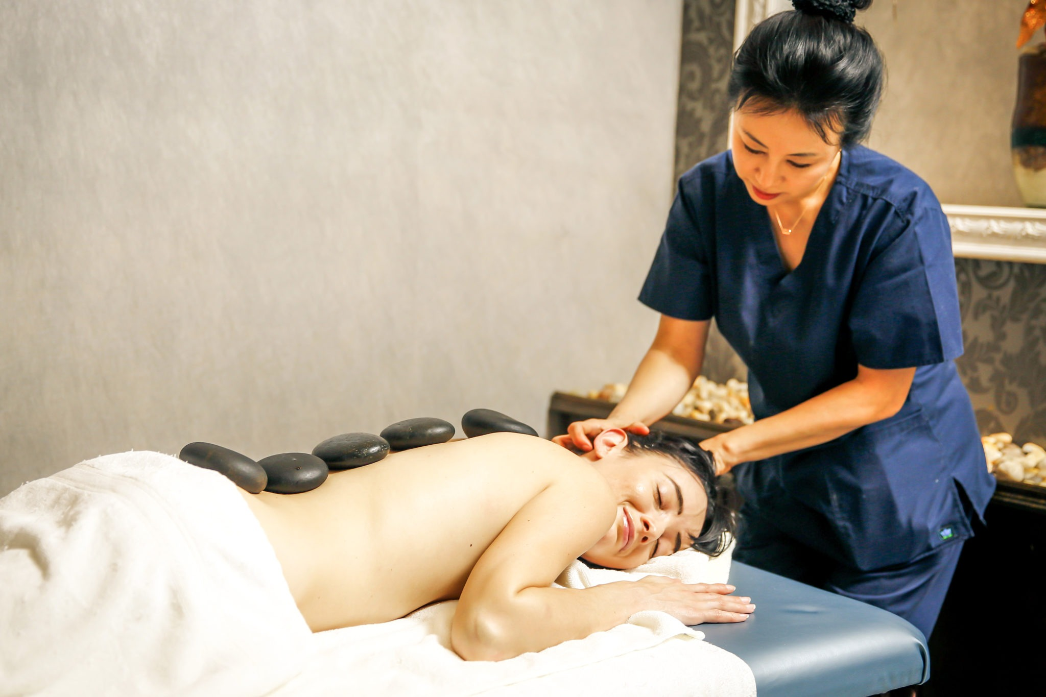 woman receiving thermo stone therapy