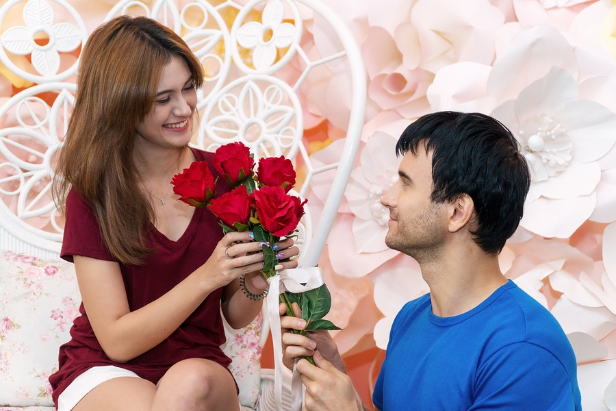 young man giving young woman red roses