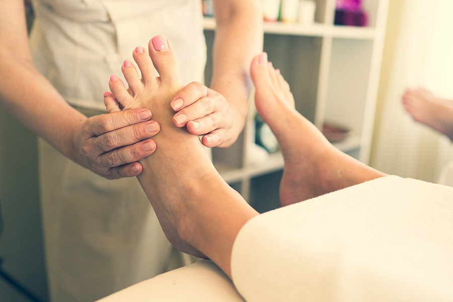 Best soothing relaxing massage, Juvenex Spa in New York, massage therapy and spa professionals, We are Open NOW! Close up of masseuse giving a foot reflexology treatment in a natural light tone in a spa salon