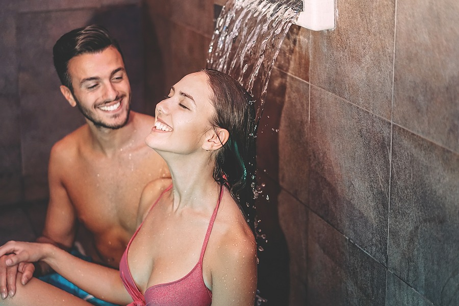 Happy couple having fun in luxury spa - Romantic young people doing relaxing wellness waterfall treatment together. The ultimate escape for couples for a special and memorable night. Perfect for couples celebrating a special occasion in New York NYC