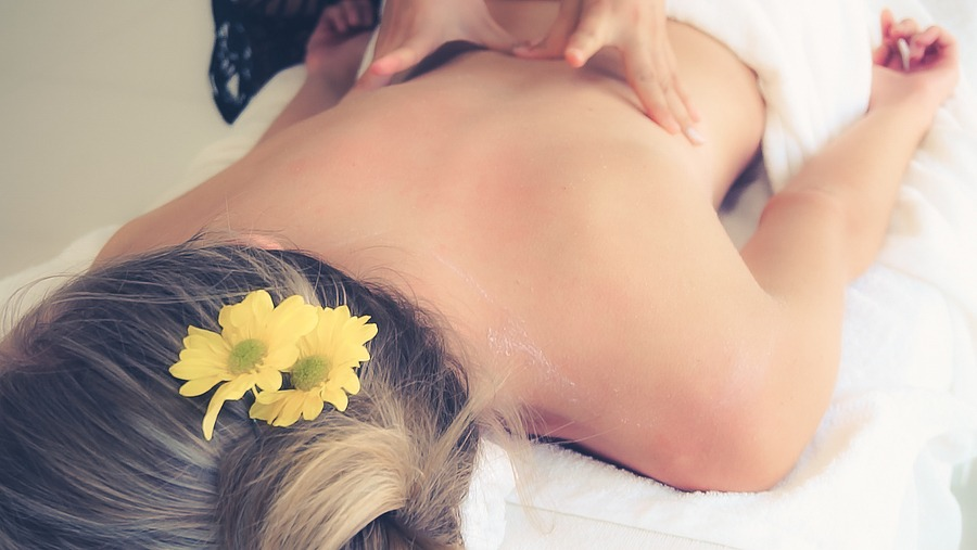 Relaxed woman getting spa massage in luxury day spa by professional massage therapist. Best soothing relaxing massage, Juvenex Spa in New York, massage therapy and spa professionals, We are Open NOW!