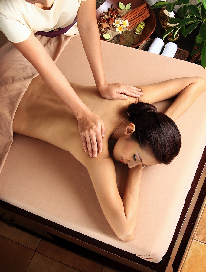 Woman in a day spa getting a deep tissue massage. Juvenex Spa in New York, Massage Indulgences, Let your stress drift away as you experience a luxurious Spa massage. We are Open NOW