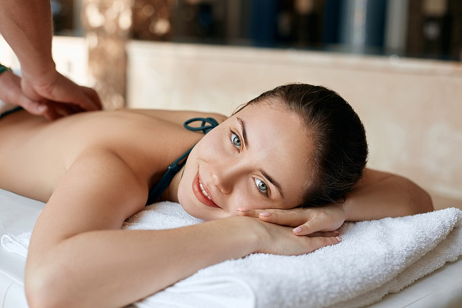 2021 All-Inclusive Getaway - Inexpensive Weekend Getaways gift card for men, Sport massage for him in Manhattan NYC, New York Beautiful young woman receiving massage in spa salon. Body care. Spa body massage woman hands treatment. Woman having massage in the spa salon