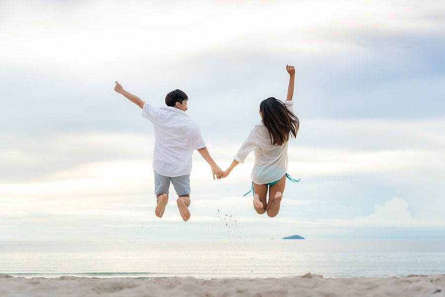 Happy couple tourists jumping on beach vacations. Travel concept of young couple cheering for summer holidays showing success, happiness, and joy on perfect white sand tropical beach under the sun. Unforgettable New Year's Eve Getaways & Celebrations … Best Getaway gift card for husband valentines ideas for him in New York City