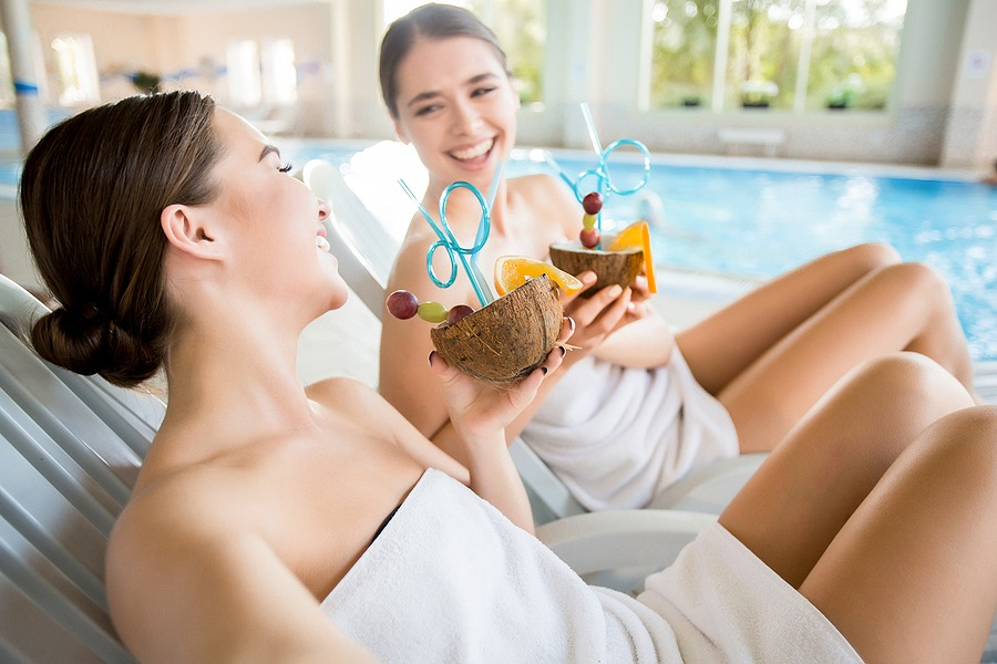 Laughing girls with tropical cocktails enjoying rest at luxurious spa resort - New York City Getaway Package - gifts card for him & Valentines day gifts for her, Facials, Spa Massage, body scrubsin New York NYC