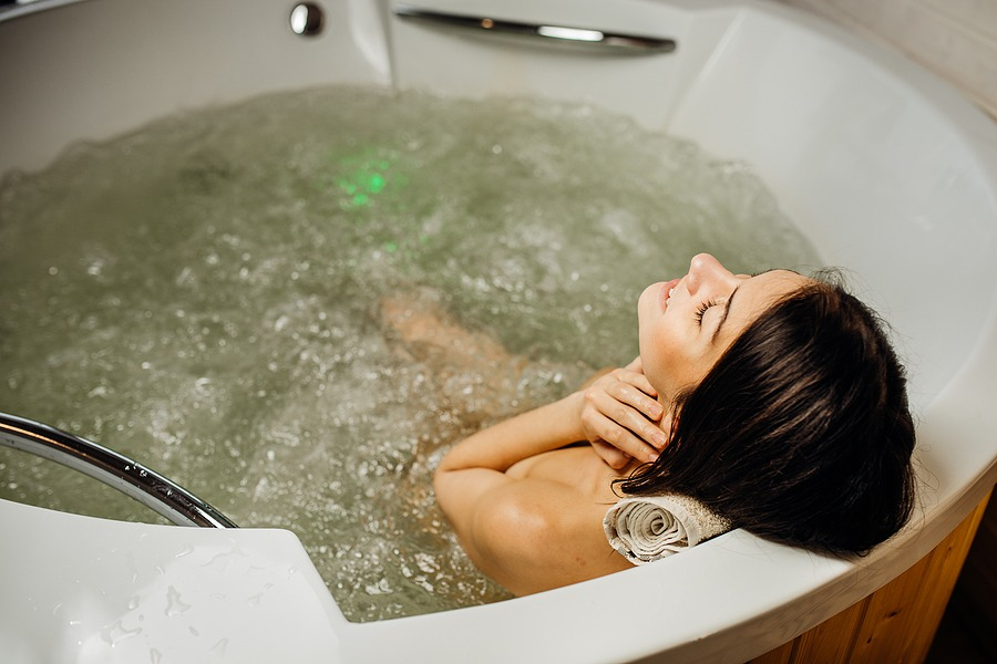 Woman relaxing at home in the hot tub bath ritual.Spa day moment in modern bathroom - 2021 All-Inclusive Getaway - Inexpensive Weekend Getaways gift card for men, Sport massage for him in Manhattan NYC, New York